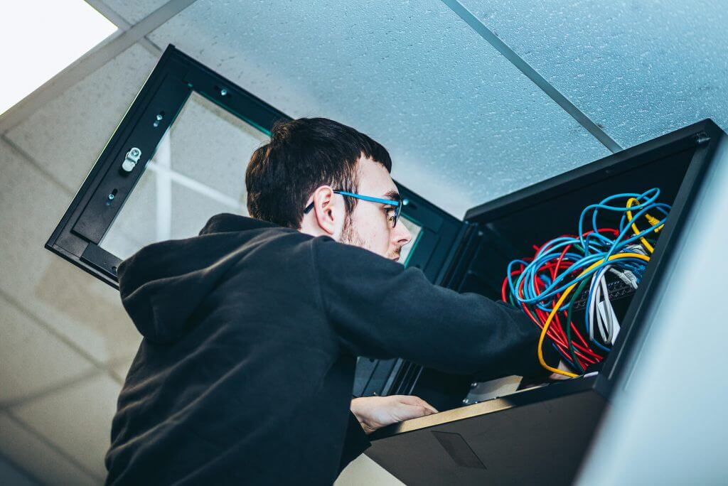 Engineer patching a network cabinet. Jupiter IT. IT support Hull